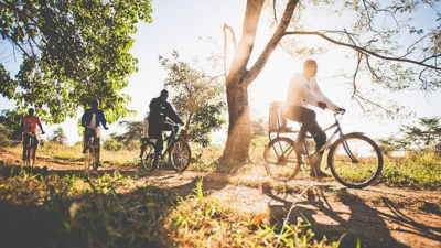 Four people riding bikes on a dirt road.