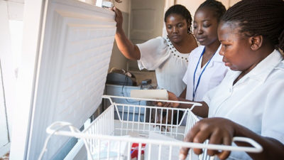 Three women ensuring refrigerators are keeping vaccines at the right temperature.